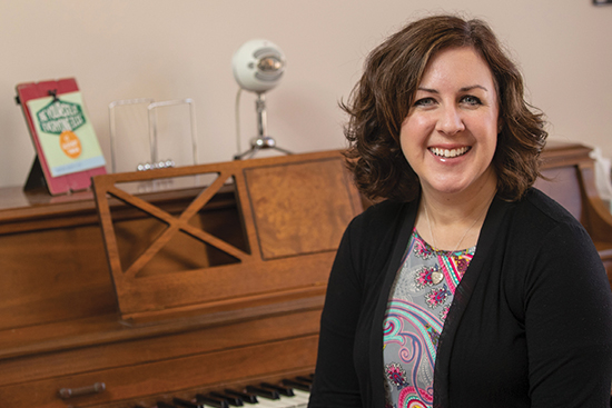 Reverend Rachele Holmes sits in front of a piano smiling.